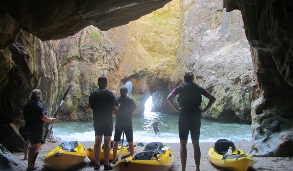 people standing in a cave with kayaks